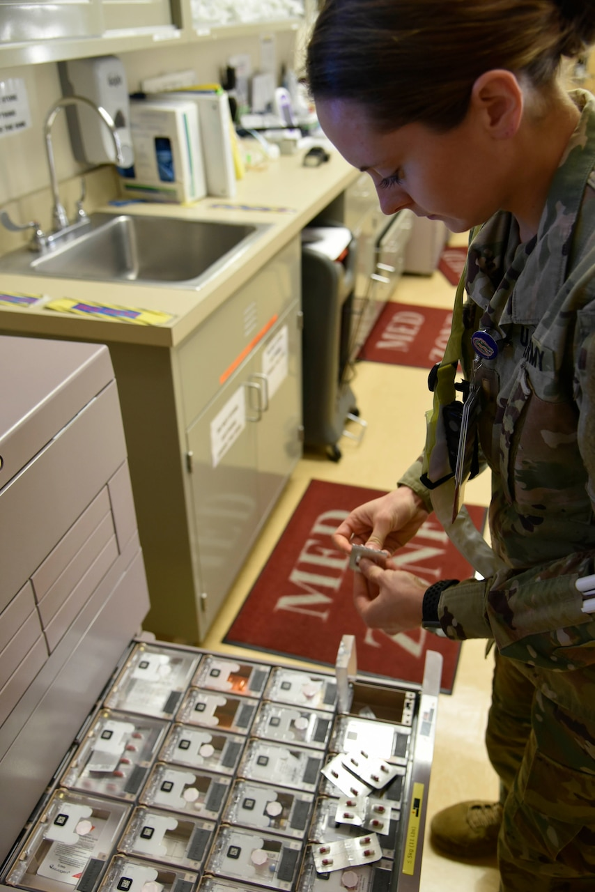 A uniformed health care provider removes medication from a metal drawer.