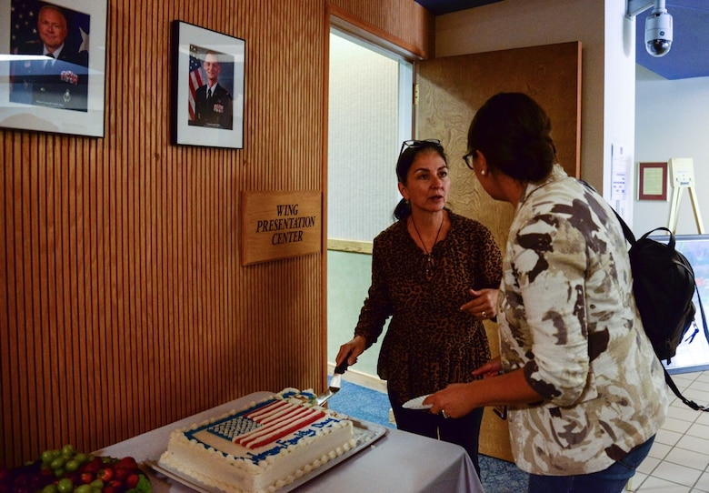 Cindy Dominguez-Trujillo, Special Assistant to the commander on Diversity and Affirmative Employment, cuts the cake during the Women's Equality Day event at Kirtland Air Force Base, N.M., August 26, 2019. During the event, audience members watched various 'TED' talks, and received remarks from the 377th Air Base Wing Commander. (U.S. Air Force photo by Senior Airman Alexandria Crawford)