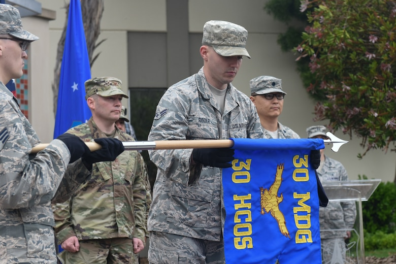 Airman First Class Thomas Ridder, Vandenberg Color Guard member, unfurls a guidon for the newly activated 30th Health Care Operations Squadron during the 30th MDG reorganization ceremony Aug. 23, 2019, at Vandenberg Air Force Base, Calif.