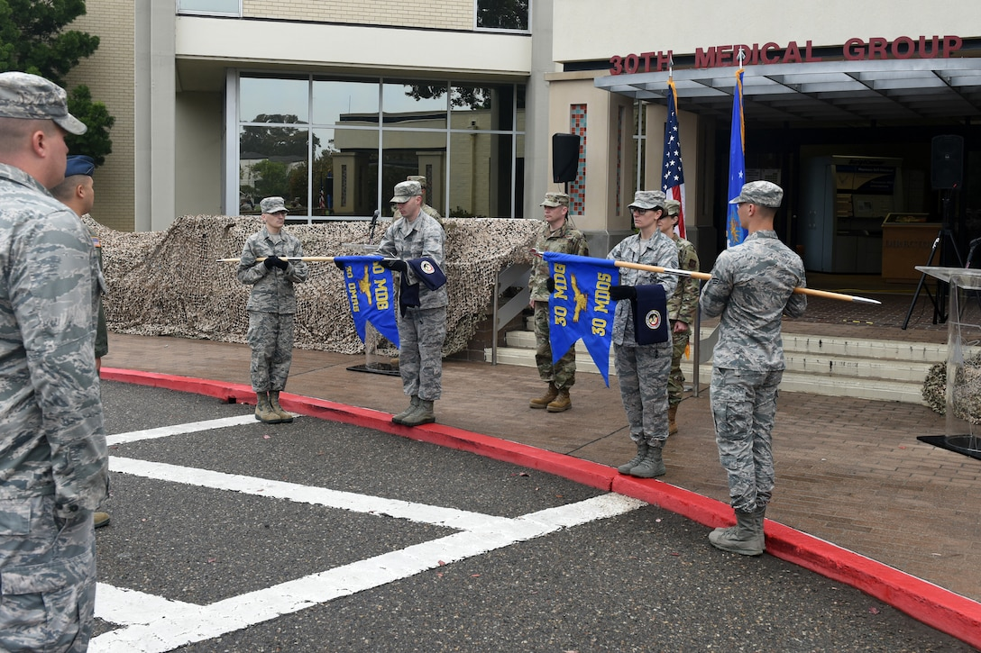 Vandenberg Color Guard team members simultaneously furl the guidon of the 30th Medical Operations Squadron and unfurl the guidon of the redesignated 30th Operational Medical Readiness Squadron during the 30th Medical Group reorganization ceremony Aug. 23, 2019, at Vandenberg Air Force Base, Calif.