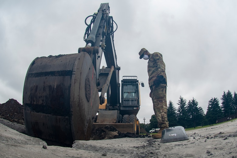 Staff Sgt. Marquette Ricardson, 8th Civil Engineer Squadron dirt boy out of Kunsan Air Base, Republic of Korea, works with a Japan Air Self-Defense Force (JASDF) engineer operating equipment to dig a hole to the proper depth during rapid airfield damage repair (RADR) during Pacific Unity 2019 at Yokota Air Base, Japan, August 22, 2019.