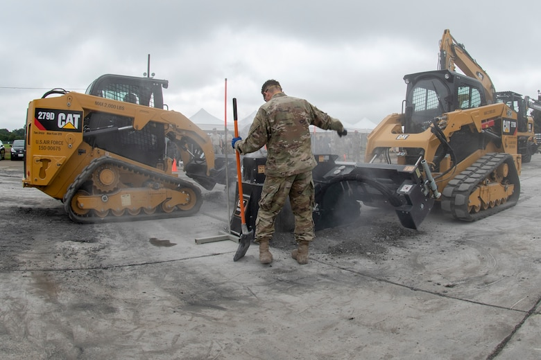 Senior Airman Tyler Crisp, 8th Civil Engineer Squadron electrical systems journeyman out of Kunsan Air Base, Republic of Korea, motions to a heavy equipment operator while conducting rapid airfield damage repair during Pacific Unity 2019 at Yokota Air Base, Japan, August 22, 2019.