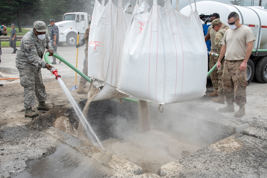 Civil Engineer Airmen mix water with flow able fill rapid set concrete to complete the backfill portion of rapid airfield damage repair (RADR) during Pacific Unity 2019 at Yokota Air Base, Japan, August 22, 2019.