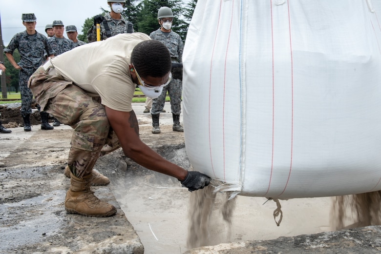 Staff Sgt. Shannon Anderson, 51st Civil Engineer Squadron electrical systems craftsman out of Osan Air Base, Republic of Korea, cuts open a bag of flow able fill rapid set concrete to be mixed with water to complete the backfill portion of rapid airfield damage repair (RADR) during Pacific Unity 2019 at Yokota Air Base, Japan, August 22, 2019.