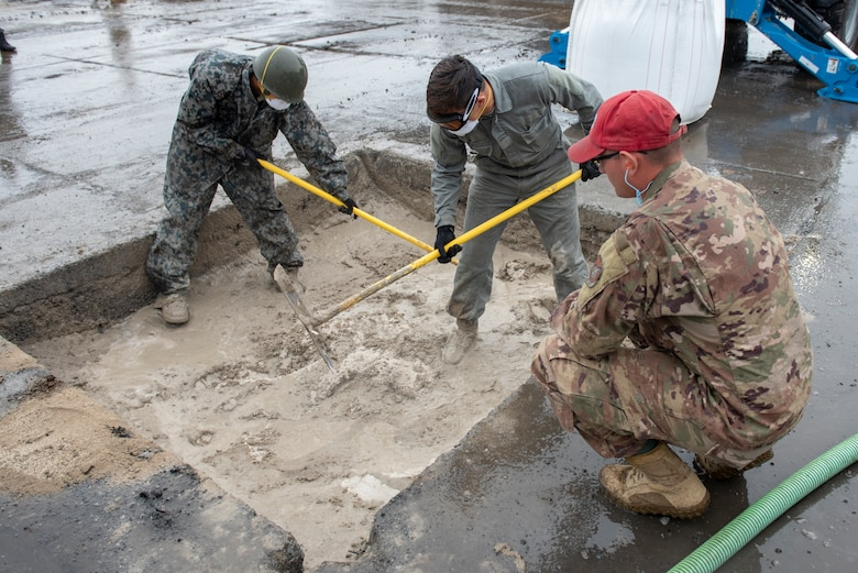 Training cadre from the 554th RED HORSE Squadron out of Andersen Air Force Base, Guam, oversees U.S. Air Force and Japan Air Self-Defense Force civil engineers mix water and flow able fill rapid set concrete to complete the backfill portion of rapid airfield damage repair during Pacific Unity 2019 at Yokota Air Base, Japan, August 23, 2019.