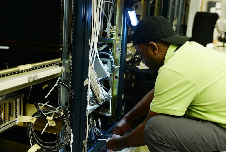Hamza Mebratie, L3Harris Technologies, cuts wire to install a new simulator Aug. 12, 2019, inside the Martin Bomber building on Offutt Air Force Base, Nebraska. This new simulator is needed in aiding Team Offutt members to perform initial, requalification and continuation training in an organized environment. Additionally the simulator will restore the ability to partake in numerous multi-organizational exercises.
