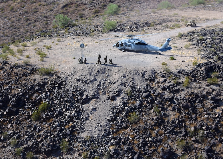 a photo of a Naval unit and helicopter sitting on a dirt training area