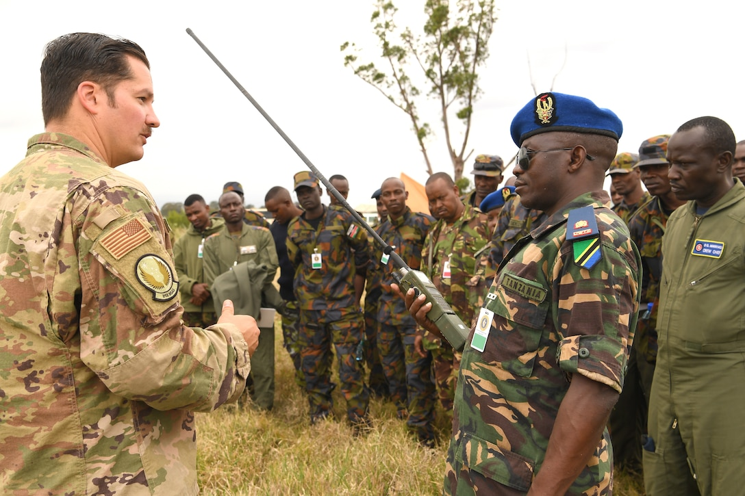 U.S. Air Force Tech. Sgt. Jared Todd, 818th Mobility Support Advisory Squadron Survival, Evasion, Resistance and Escape air advisor, and Tanzania Air Force Command Col. Ian Haule, an aircraft maintenance engineer, discuss radio communication techniques at the African Partnership Flight Kenya 2019, Laikipia Air Base, Kenya, August 22, 2019.