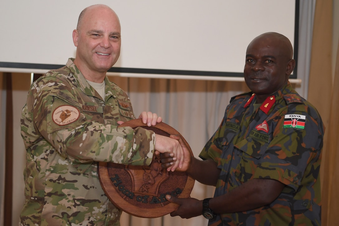 U.S. Air Force Brig. Gen. James R. Kriesel, Combined Joint Task Force—Horn of Africa deputy commanding general, exchanges gifts with Kenya Air Force Brigadier John Omenda, base commander at Laikipia Air Base, during the closing ceremony for African Partnership Flight Kenya 2019, Nanyuki, Kenya, August 25, 2019.