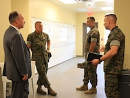 U.S. Marine Corps Col. Corey M. Collier, right, the Marine Corps Security Force Regiment commanding officer, speaks to Gen. Robert F. Hedelund, center left, the U.S. Marine Corps Forces Command commanding general, during a visit to MCSFR at Naval Weapons Station Yorktown, Virginia, Aug. 27, 2019. The leaders spoke about MCSFR's mission and capabilities as the largest Marine Corps regiment with 11 subordinate units in 8 locations throughout the world to include Bahrain, Cuba, Japan, and Spain. (U.S. Marine Corps photo by Sgt. Jessika Braden/ Released)