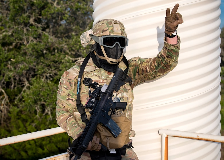 Maj. Zach Reinbold, 3d Weather Squadron Det 1 commander, signals his fellow Airmen during a certification field exercise (CFX), July 29, 2019, at Camp Bowie Training Center, Texas. The CFX was designed to evaluate the squadron's overall tactical ability and readiness to provide the U.S. Army with full spectrum environmental support to the Joint Task Force (JTF) fight. The CFX immersed Airmen into all the aspects of what could come with a deployment such as force on force scenarios. (U.S. Air Force photo by Airman 1st Class Eugene Oliver)