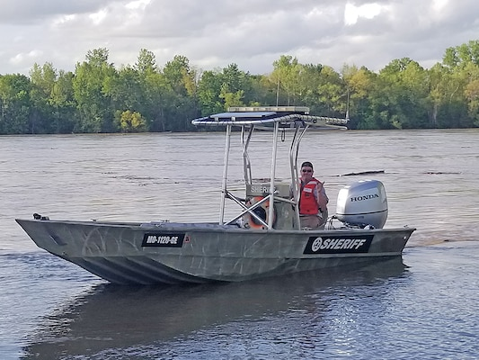 A deputy from Missouri's Osage County Sheriff office operates a former Coast Guard vessel during spring floods. The craft was obtained through the 1033 program that is administered through DLA Disposition Services.