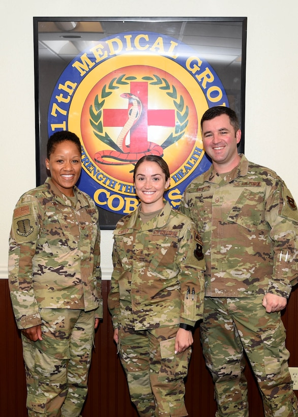 U.S. Air Force Airman 1st Class Breanna Carter, 17th Medical Group family practice medical technician, center, is recognized by Col. Lauren Byrd, 17th Medical Group commander, left, and Master Sgt. Steven Baer, 17th Medical Operations Squadron superintendent, right, as July's Medic of the Month at the Ross Clinic on Goodfellow Air Force Base, Texas, August 19, 2019.  Carter has led multiple safety huddles and crafted schedules to maximize team efficiency for over 400 patients. (U.S. Air Force photo by Airman 1st Class Abbey Rieves/Released)