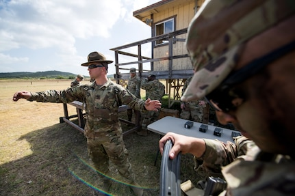 U.S. Army Sgt. 1st Class William Hale (left), Company F, 232nd Medical Battalion range safety officer, from Joint Base San Antonio-Fort Sam Houston, hands out ammunition for the M4 stress shoot event during the Army Drill Sergeant of the Year Competition Aug. 20 at JBSA-Camp Bullis.