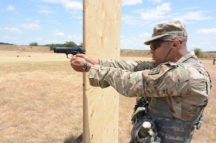 Staff Sgt. Jeffrey C. Lullen, Health Readiness Center of Excellence at Joint Base San Antonio-Fort Sam Houston, firing an M9 at the mystery event. In this lane while firing from the standing, kneeling, and prone positions the competitors first fired the M4 rifle then transitioned to the M4 pistol.