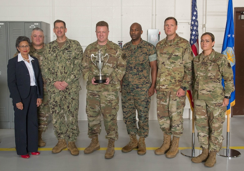 U.S. Air Force Col. Jeffrey Schreiner, center, holds the Omaha Trophy with the U.S. Strategic Command official party after the awards presentation on Aug. 27, 2019, at Whiteman Air Force Base, Missouri. The Omaha Trophy is awarded by the Strategic Command Consultation Committee to units for excellence in strategic deterrence and support of global strike operations. The active-duty 509th Bomb Wing and Missouri Air National Guard's 131st Bomb Wing jointly earned the Omaha Trophy for executing the best Strategic Bomber Operations of 2018. From left, the Honorable Rita Sanders, representing the SCC; U.S. Air National Guard Col. Kenneth Eaves, 131st Bomb Wing commander; U.S. Navy Vice Adm. Dave Kriete, STRATCOM deputy commander; Col. Jeffrey Schreiner; U.S. Marine Corps Master Gunnery Sgt. Terrence Meekins, STRATCOM Headquarters commandant; U.S. Air Force Chief Master Sgt. Ziegelbein, acting command chief 509th Bomb Wing and Chief Master Sgt. Jessica Settle, 131st command chief. (U.S. Air Force Photo by Airman 1st Class Thomas Johns)