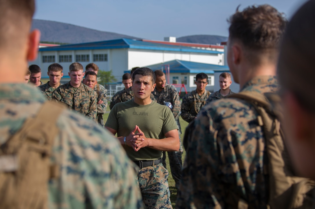 A Marine stands in the middle of a circle of Marines.