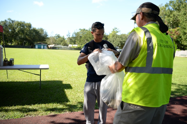 U.S Air Force Airman 1st Class Ferimix Plasencia, 336th Training Squadron client systems student, throws away trash during the Community Clean-Up Day in Ocean Springs, Mississippi, Aug. 24, 2019. Volunteers coming from Ocean Springs and Keesler Air Force Base took to the streets of Ocean Springs to pick up trash around the city. (U.S Air Force photo by Airman 1st Class Spencer Tobler)