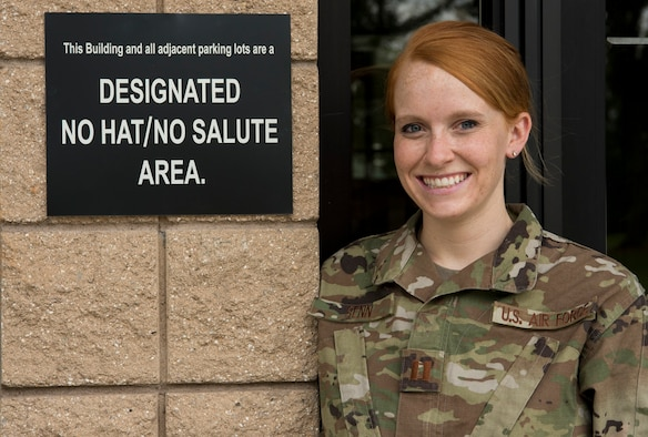 U.S. Air Force Capt. Emilee Senn, 337th Recruiting Squadron operations flight commander, stands next to a designated No Hat/No Salute area sign at the 20th Force Support Squadron Child Development Center at Shaw Air Force Base, South Carolina, Aug. 27, 2019.
