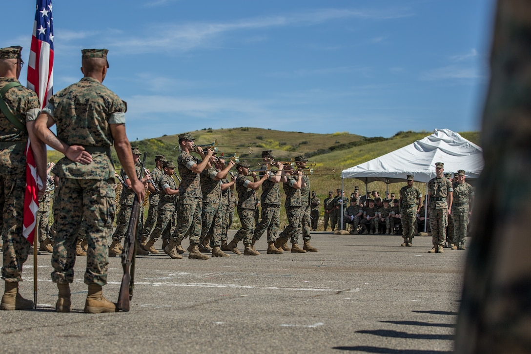 A military band marches and performs as other service members watch.