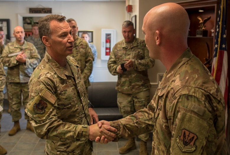 U.S. Air Force Maj. Gen. Chad Franks, Ninth Air Force commander, coins Master Sgt. Christopher Moore, 733rd Logistics Readiness Squadron fuels information center section chief, during a visit at Joint Base Langley-Eustis, Virginia, August 26, 2019.