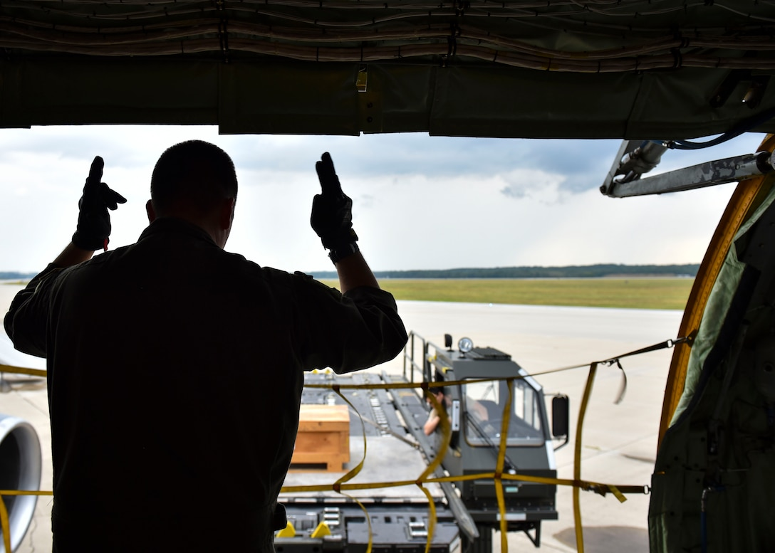 U.S. Air Force Master Sgt, Joseph Ekker signals to Kevin Shaffer, Data Monitor Systems material handler