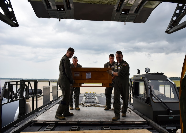 U.S. Air Force Airmen from the 97th Air Refueling Squadron move a box of memorabilia onto a KC-135 Stratotanker