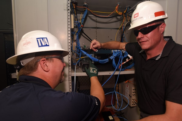Rich Ellis (Left), field engineer with the Tennessee Valley Authority Region 1 Information Technology Field Services, and Bradley Gatewood, U.S. Army Corps of Engineers Nashville District Information Technology chief, make the final fiber optic connection to Joe Wheeler Lock, increasing bandwidth and data transmission speeds. The Nashville District operates and maintains the lock at the TVA project in Rogersville, Ala. The two agencies are partnering to establish fiber optic connections at all 10 lock project sites on the Tennessee River and Clinch River. (USACE Photo