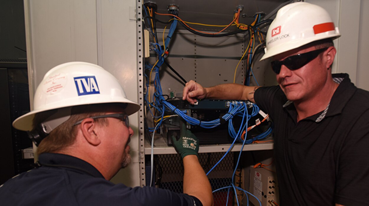 Rich Ellis (Left), field engineer with the Tennessee Valley Authority Region 1 Information Technology Field Services, and Bradley Gatewood, U.S. Army Corps of Engineers Nashville District Information Technology chief, make the final fiber optic connection to Joe Wheeler Lock, increasing bandwidth and data transmission speeds. The Nashville District operates and maintains the lock at the TVA project in Rogersville, Ala. The two agencies are partnering to establish fiber optic connections at all 10 lock project sites on the Tennessee River and Clinch River. (USACE Photo by Lee Roberts)