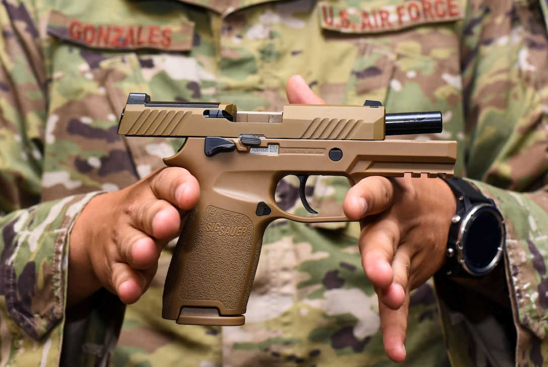Staff Sgt. Will Gonzales, 36th Security Forces Squadron armory NCO in charge, displays a Sig Sauer M18 pistol on Andersen Air Force Base, Guam, Aug. 26, 2019.