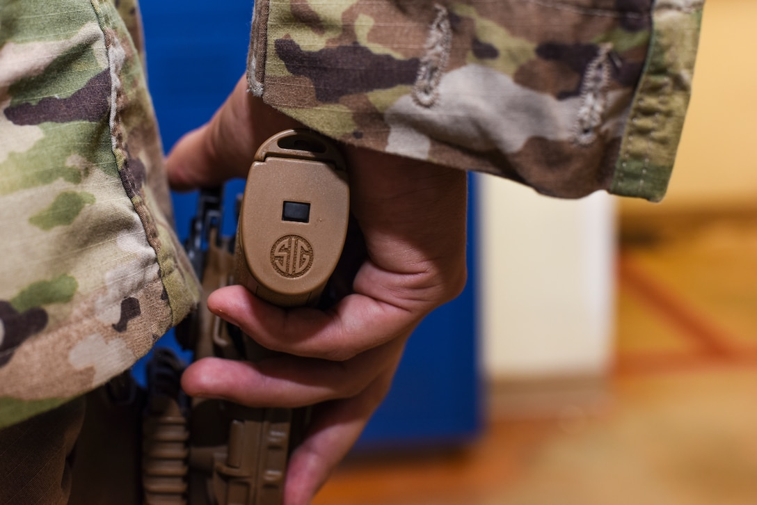 Staff Sgt. Will Gonzales, 36th Security Forces Squadron armory NCO in charge, holsters a Sig Sauer M18 pistol on Andersen Air Force Base, Guam, Aug. 26, 2019.
