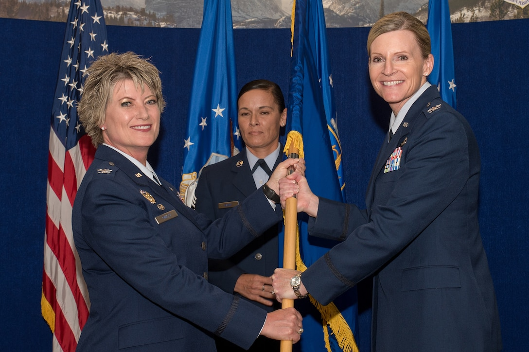 Col. Amy J. Boehle (right), Headquarters Individual Reservist Readiness and Integration Organization (HQ RIO),commander, receives the guidon from Col. Kelli B. Smiley (left),  Commander Air Reserve Personnel Center, during an assumption of command ceremony Aug. 28, 2019, at Buckley Air Force Base, Colo. As the HQ RIO commander, Boehle is responsible for seamlessly integrating over 8,000 wartime-ready Individual Reserve forces in more than 50 MAJCOMs, COCOMs, and government agencies to meet Air Force and Combatant Commander requirements. (U.S. Air Force photo by Master Sgt. Eric Amidon)