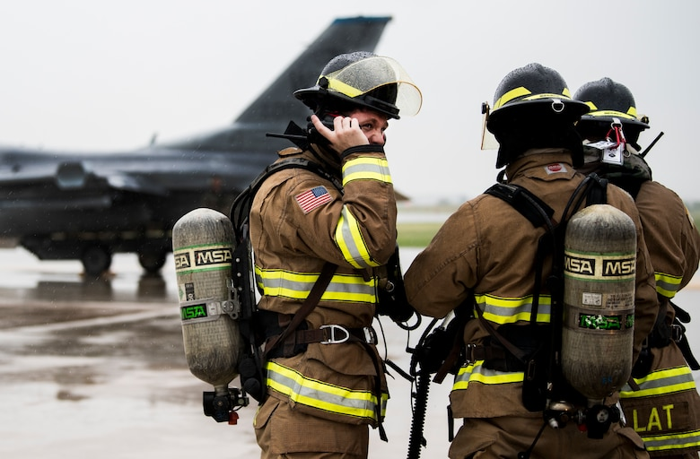 U.S. Air Force Airmen from the 8th Civil Engineer Squadron fire department talk on their radios during training at Kunsan Air Base, Republic of Korea, Aug. 27, 2019. The training gave first responders and maintenance professionals the opportunity to respond to a U.S. Air Force F-16 Fighting Falcon emergency landing. (U.S. Air Force photo by Senior Airman Stefan Alvarez)
