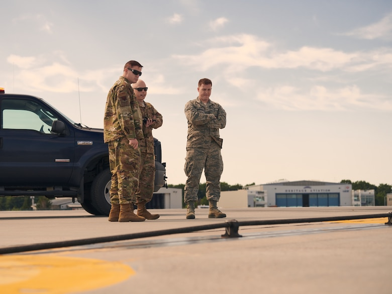 U.S. Air Force Master Sgt. Darren Adams, center, and Staff Sgt. Joseph Mailloux, right, both assigned to the airfield management section of the 158th Operations Group, 158th Fighter Wing, Vermont Air National Guard, inspect an arresting cable on the flightline at the Burlington Air National Guard Base, Vt., Aug. 3, 2019. This arresting cable can quickly be raised on the runway and grab onto a hook attached to fighter aircraft to help it stop in the event of an emergency landing. (U.S. Air National Guard photo by Tech. Sgt. Ryan Campbell)