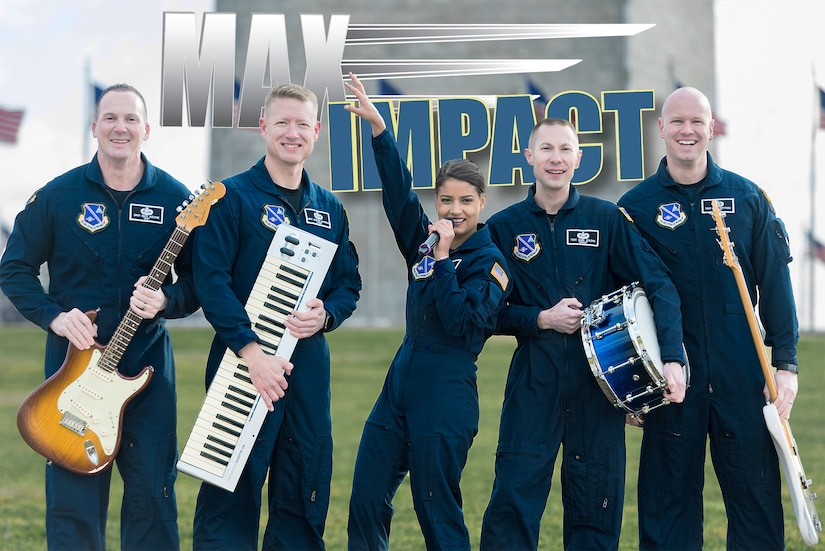 Five airmen wearing flight suits who make up the rock band Max Impact pose on a field with their respective instruments.