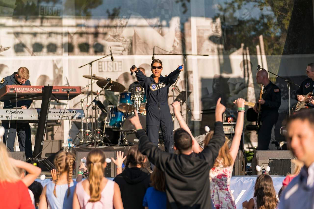 A singer on stage in a flight suit points both fingers toward the crowd looking at her.
