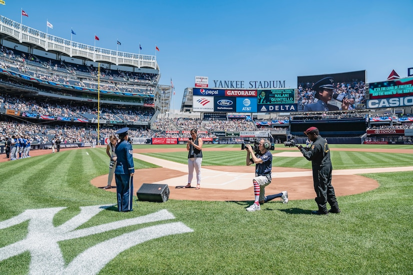 An airman in dress blues prepares to sing near the New York Yankees logo on the field at Yankees Stadium while four cameramen film her.