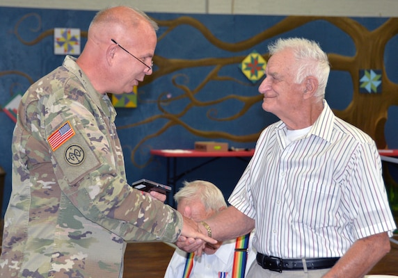 Maj. Gen. Ray Shields, the adjutant general of New York, presents a military challenge coin to Air Force Korean War veteran Merton W. Houghton during an awards ceremony at the former New York State Armory in Hoosick Falls, N.Y., on Aug. 28, 2019. Shields honored 10  local veterans with New York state awards recognizing their military service during the event.