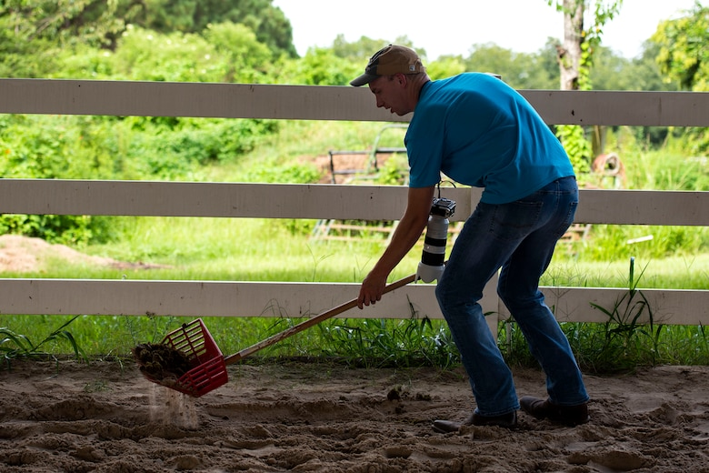 Capt. John Roling, 71st Rescue Squadron operations flight commander, helps clean up a corral at a therapeutic riding center Aug. 20, 2019, in Hahira, Ga. Roling, like many Airmen, does volunteer work for various organizations in the local community. Through his two passions of photography and helping people, he's able to provide a free photo service as well as any assistance needed for the organizations he participates with. (U.S. Air Force photo by Senior Airman Erick Requadt)