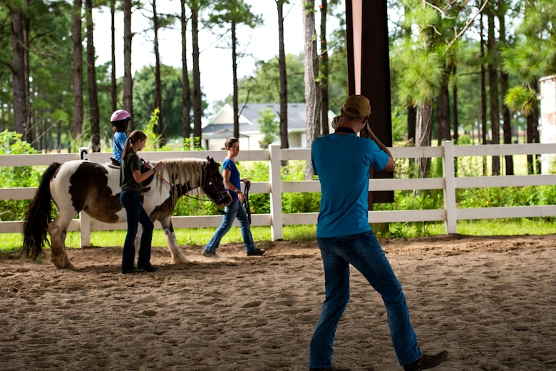 Capt. John Roling, 71st Rescue Squadron operations flight commander, photographs a participant at a therapeutic riding center Aug. 20, 2019, in Hahira, Ga. Roling, like many Airmen, does volunteer work for various organizations in the local community. Through his two passions of photography and helping people, he's able to provide a free photo service as well as any assistance needed for the organizations he participates with. (U.S. Air Force photo by Senior Airman Erick Requadt)