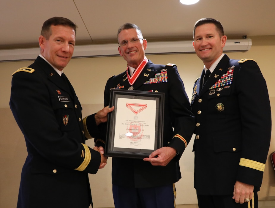 ​E. Scott Lowdermilk (center), the Transatlantic Division Chief of Plans and Operations, receives the Army Engineer Association's Silver Order of the de Fleury Medal at his retirement ceremony from both the military and civilian service on Aug. 2, 2019, after a career that spanned 38 years. Presenting the award to Lowdermilk are Maj. Gen. Donald Jackson (left) and Maj. Gen. Robert Carlson (right).
