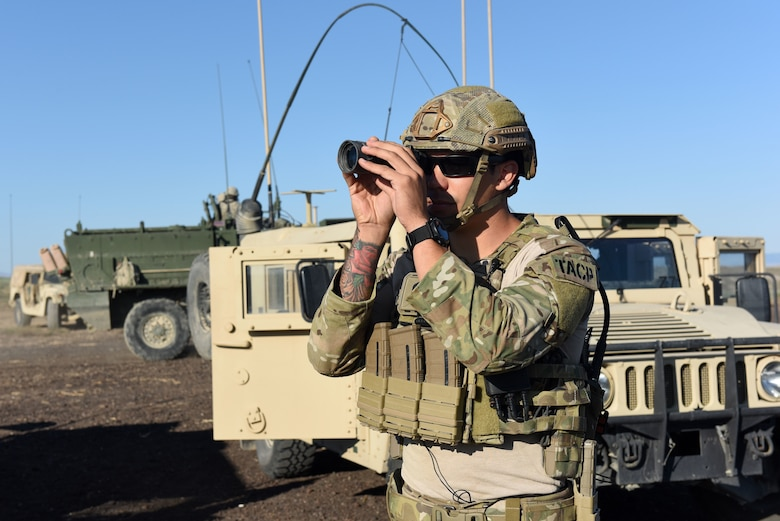 Senior Airman Ian Samodio uses a monocular to positively identify a target.