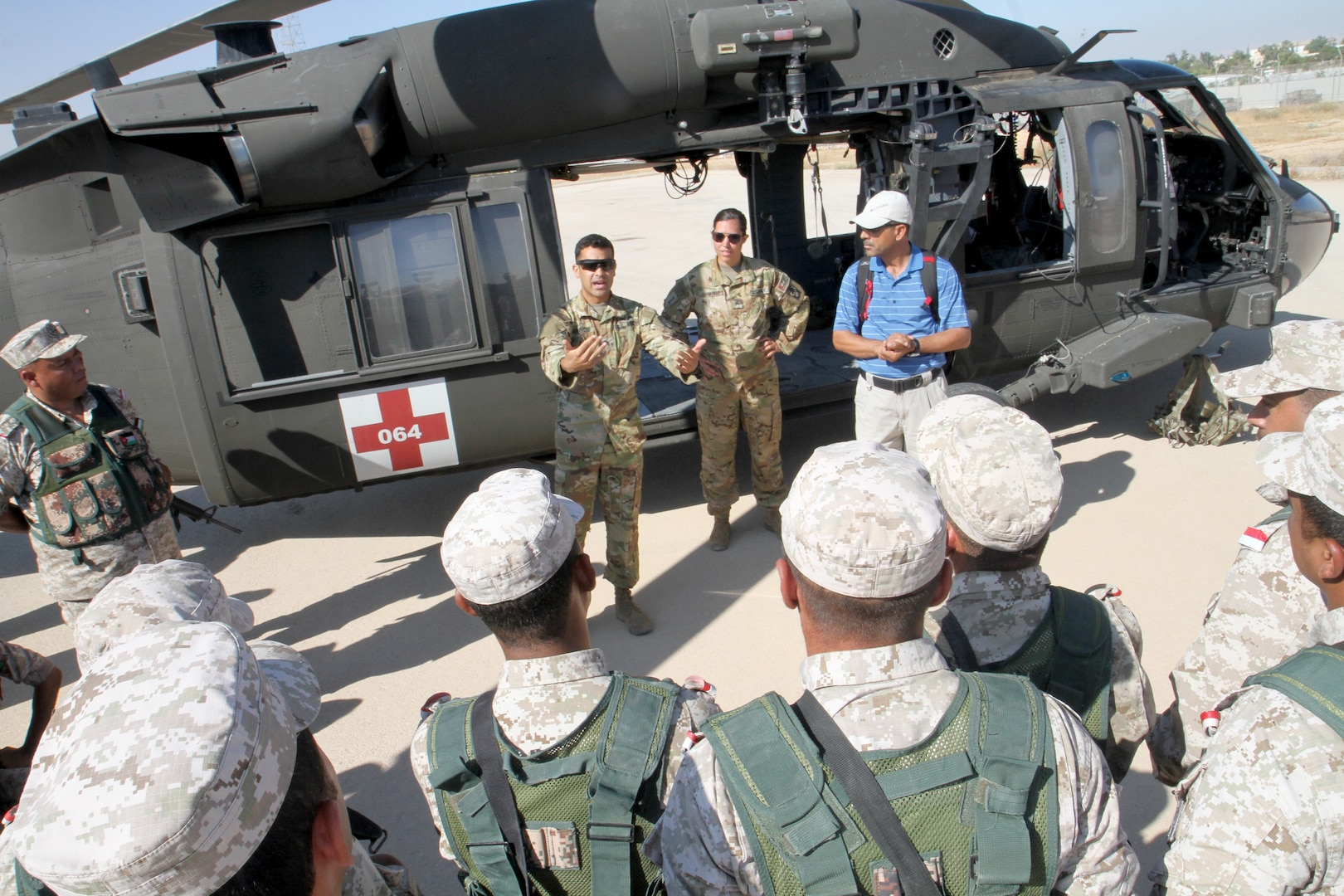 U.S. Army Sgt. Ignacio Aparicio, center, crew chief, Golf Company, 5th Battalion, 159th Aviation Regiment, talks to members of Jordan Armed Forces' 7th Mechanized Infantry Battalion about hand signals and casualty loading procedures during medical evacuation training in preparation for exercise Eager Lion 2019, Aug. 21, 2019. This multinational exercise is U.S. Central Command's premiere exercise in the Levant region and is a major training event that provides U.S. forces, Jordan Armed Forces and 28 other participating nations the opportunity to improve their collective ability to plan and operate in a coalition-type environment. (U.S. Army Reserve photo by Sgt. Zach Mott)