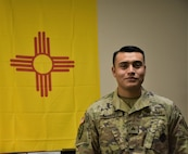 Sgt. Ignacio Alvarez, recruiter, Gallup Recruiting Station, Albuquerque Recruiting Company, Phoenix Recruiting Battalion, poses in front of the New Mexico state flag in his recruiting station, Gallup, N.M., Aug. 22. Alvarez, a Gallup native, returned to his hometown as a recruiter in Nov. 2017, having left 6 years earlier to join the Army.