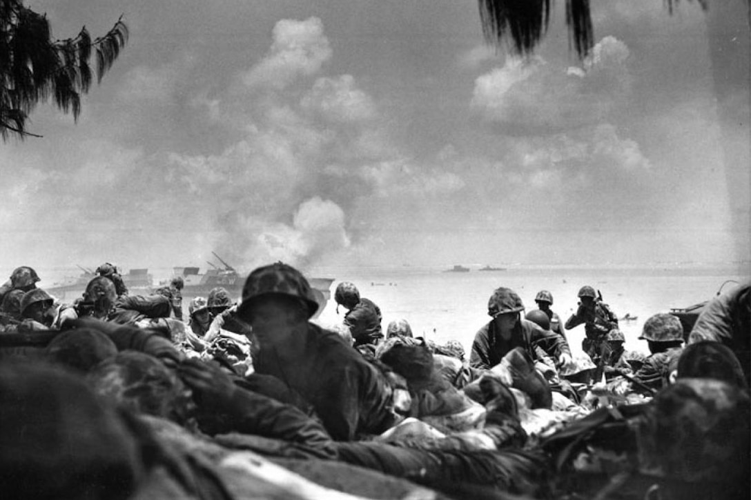 Marines move inland from the sea during battle.