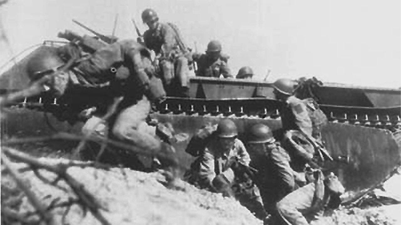 Troops wade onto beach.