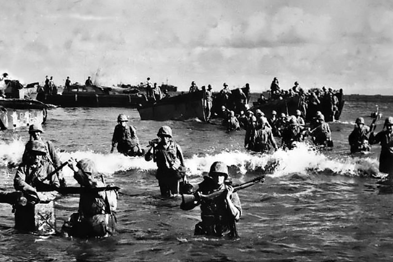 Marines wade onto beach.