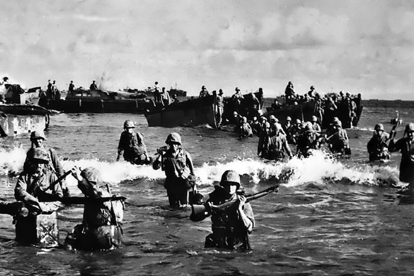 Marines wade onto beach.