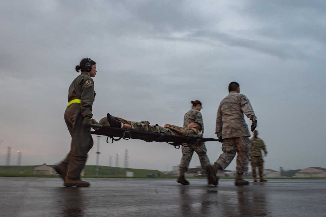 U.S. Air Force personnel assigned to the 374th Medical Group, Yokota Air Base, Japan carry simulated patients out of a C-130J Super Hercules, Aug. 28, 2019. They moved and treated more than 30 U.S. Army personnel off the aircraft as part of Operation Ascendant Eagle, a joint patient movement exercise held between Osan Air Base, Korea and Yokota. (U.S. Air Force photo by Staff Sgt. Kyle Johnson)