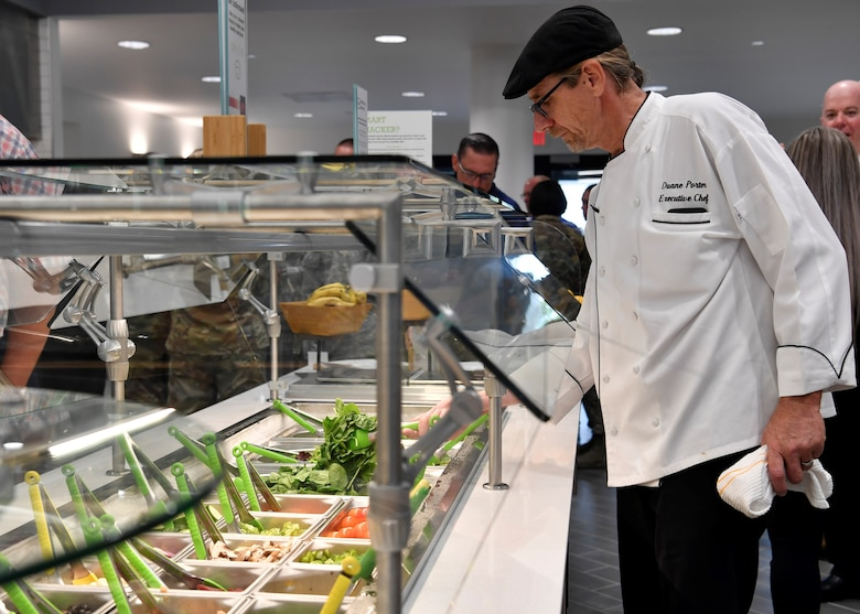 Duane Porter, 87th Force Support Squadron executive chef, prepares the salad bar for customers to use during the re-opening of the Halvorsen Hall Dining Facility on Joint Base McGuire-Dix-Lakehurst, New Jersey, Aug. 27, 2019. The updated menu includes a pizza bar, super-sonic sub sandwiches and a salad bar that fall in line with the Air Force initiative Food 2.0, providing more food options that are also healthier. An additional change also includes utilization of the DFAC for all Joint Base MDL community members.